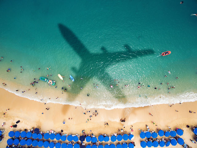 Aerial view of a blue-green beach with swimmers and the shadow of an airplane.